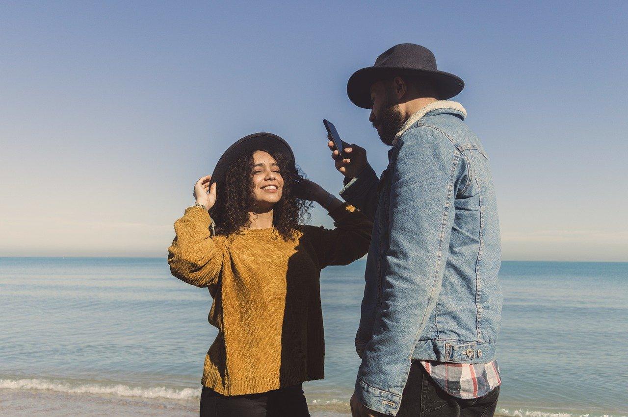 浜辺で女性の写真を撮る男性