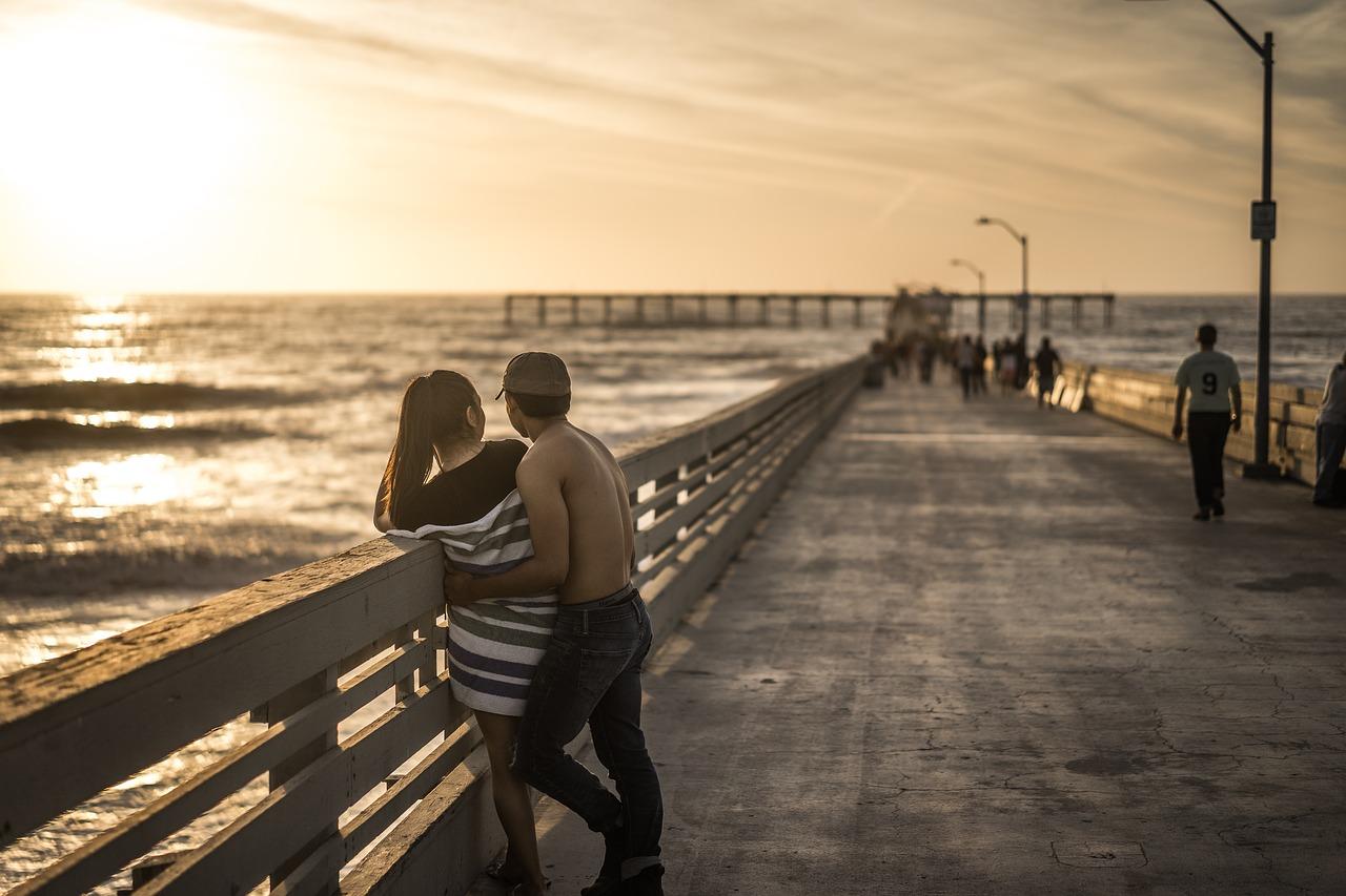 夕方の桟橋で抱き合うカップル