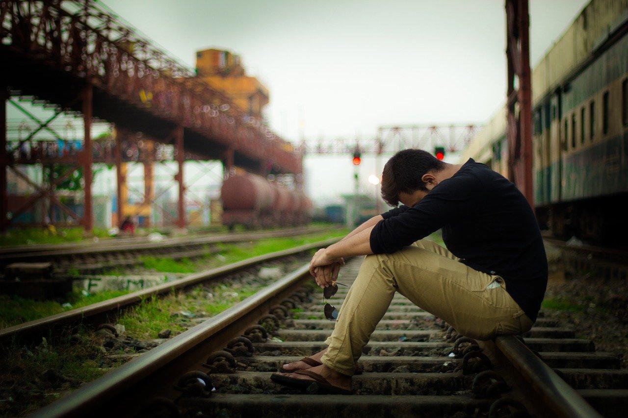 線路でうつむく男性